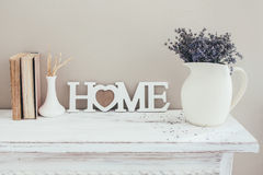 Shabby chic interior decor. For farmhouse. Lavender in pitcher, books and wooden letters on a vintage shelf over pastel wall. Provence home decoration royalty free stock image