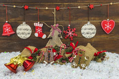 Shabby chic rustic Christmas decorations. On brown wooden board and snow Royalty Free Stock Photo