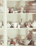Shabby chic style dishware. Rustic shabby chic style dishware in the kitchen chest of drawers royalty free stock photography