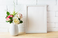 Shabby chic style white frame mockup with pink roses. Empty white frame mockup for design presentation. Portrait or poster white frame mockup stock photography