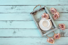 Shabby chic tray. Vintage wooden tray with porcelain teacup and rose buds on shabby chic mint background, top view point stock photos