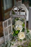 Shabby chic wedding decor with repurposed lantern cage. Old, vintage candle cage or lantern repurposed as a rustic, shabby chic wedding decor with white flowers Stock Photo