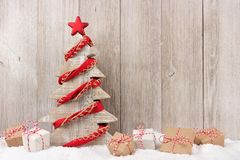 Wooden Christmas tree with red garland and gifts against wood Stock Photography