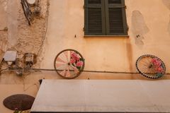 Two colorful wheels as decoration of a house in Alghero, Italy. A shabby façade of on old house in Alghero on the Italian island of Sardinia is decorated with royalty free stock image