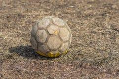 Shabby football (soccer ball) on a very dried grass Stock Photography