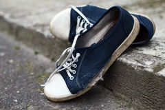 Shabby holey gumshoes. Shabby textile holey blue gumshoes with white laces had abandoned at the street in summer Royalty Free Stock Image
