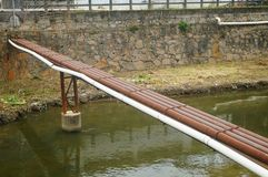 A shabby long steel pipe bridge over the river Royalty Free Stock Photography