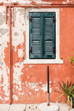Shabby orange wall and green window shutters Royalty Free Stock Photography