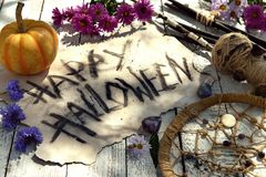 Shabby paper with text Happy Halloween, voodoo doll, pumpkin and last autumn flowers royalty free stock photos