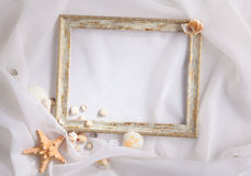 Shabby picture frame and shells. On white fabric Stock Image