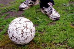 Shabby poor soccer ball and legs Stock Photo