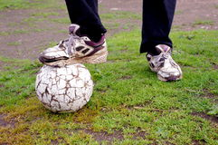 Shabby poor soccer ball and legs Stock Image
