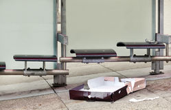 Shabby Public Bus Stop. Dirty bus stop with litter, trash, empty seats, and liquor bottle Stock Image
