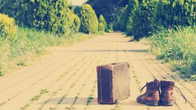 Shabby shoes, antique suitcase, a yellow brick road. Nashville effect. Old shabby leather shoes, next to an antique suitcase with reinforced metal corners, in stock photos
