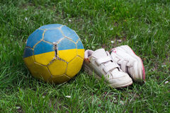 Shabby soccer ball and a children`s sports shoes Stock Images