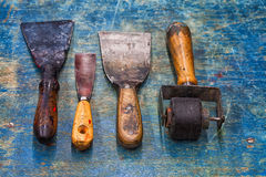 Shabby used artist tools: black rubber roller, big and small putty knives on blue paint wooden background. Diy Royalty Free Stock Photo
