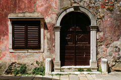 Shabby wall of the building with a maroon door and window with shutters in Porec, Croatia Stock Images