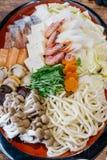 Shabu-shabu集合包括大虾、豆腐、圆白菜、薤、乌龙面、三文鱼、攫夺者、扇贝、芹菜、椎茸和白色山毛榉蘑菇 免版税库存图片