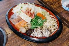 Shabu-shabu集合包括大虾、豆腐、圆白菜、薤、乌龙面、三文鱼、攫夺者、扇贝、芹菜、椎茸和白色山毛榉蘑菇 免版税库存照片