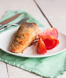 Shad grilled fish with tomato on a plate, green napkin Stock Photo