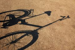 Shade of a bicycle on a asphalt. Royalty Free Stock Photos