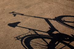 Shade of a bicycle on a asphalt. Royalty Free Stock Photo