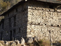 Shade and Light. A house made of rocks with sun shining brightly on one side Royalty Free Stock Image