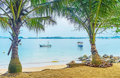 The shade of palm trees. The view on the shore of Jungle Beach with pleasure boats through the shady palms on the sand, Unawatuna, Sri Lanka royalty free stock images