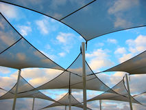 Shade Sails. Modern shade sails in a pattern in front of a blue cloudy sky royalty free stock image