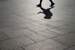 Shade on the street. Black and white image a a walking person with the shade upside down royalty free stock image
