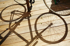 Shade of wheels. Shadow of bicycle on wooden terrace Royalty Free Stock Image