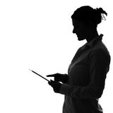 Shade woman. A picture of a shade of a woman working on tablet over white background stock photos
