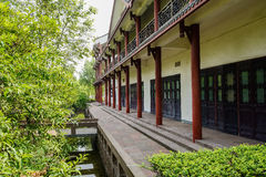 Shaded Chinese colonnade by brook in sunny summer Stock Photo