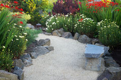 Shaded Crocosmia Path. A curved garden path edged with stones winds through a perennial garden with crocosmia and dasies royalty free stock photos