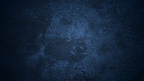 Shaded deep blue background. Old cracked surface. Aged flaking dyed leather texture. Peeled skin texture under soft navy blue light stock photography