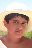 Shaded, Handsome Boy. Latino boy wearing straw hat, which shades his eyes and chest and protects him from being burned Royalty Free Stock Photography