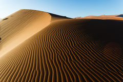 Shaded Namibian desert dunes sand ripple pattern rises to ridge. Royalty Free Stock Photo