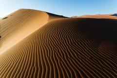 Shaded Namibian desert dunes sand ripple pattern rises to ridge. Shaded Namibian desert dunes sand ripple pattern rises to top ridge. This African desert is the Royalty Free Stock Photo