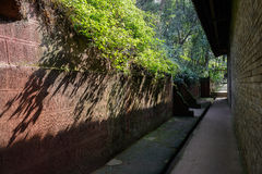 Shaded passageway behind ancient Chinese building on sunny day Stock Photo