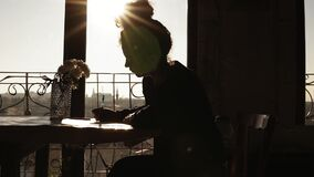 Shaded by the sun, figure of young creativefemale artist drawing something, sitting by the table with beautiful flowers. On it. Inspiring art craft stock footage