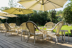 Shaded table and chairs on planked floor near lawn of courtyard Stock Photo