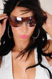 Shades. Female fashion model wearing a pair of sun glasses tht she has just put on as she is still holding the frame Stock Photos