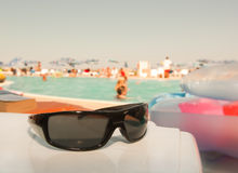Shades. Black designer sunglasses in a poolside location Stock Image