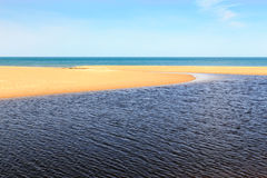 Shades of Blue. An outflow cuts through the sand as it converges with the blue waters of Lake Michigan at Indiana Dunes State Park Royalty Free Stock Photography