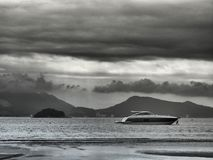 Shades of gray around a power boat by the beach at the end of th. Luxurious power boat by the beach at the end of the day royalty free stock images