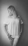 Shades of grey. Blond woman standing by the wall stock photo
