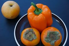 Fruit and vegetable still life in orange and black tones stock photo