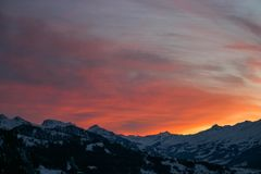Shades of orange and pink clouds explode over the snow-capped Alps in this epic mountain sunset stock photography
