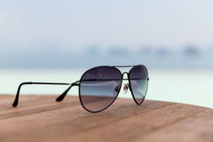 Shades or sunglasses on table at beach. Travel, tourism, summer vacation and fashon accessories concept - shades or sunglasses on table at beach Royalty Free Stock Photography