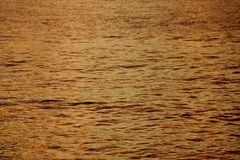 Shades of Yellow-orange Ocean Water ripples off the North Shore of Oahu reflecting dusk light Stock Photo